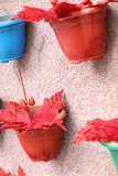 Colorful pots with red leaves stock images