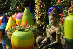 Colorful pots and statue. Large colorful pots and a carved, female statue Stock Photos