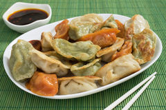 Colorful Potstickers. Fried jiaozi, or Chinese potstickers, wrapped in plain, tomato, and spinach dough. Served with a soy sauce and chili dipping sauce Royalty Free Stock Images