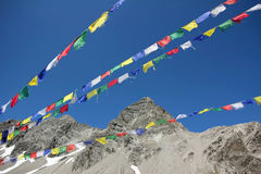 Colorful prayer flags and mountain peak against blue sky Stock Photo
