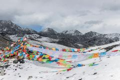 Colorful prayer flags on snow mountain. In winter Stock Photos