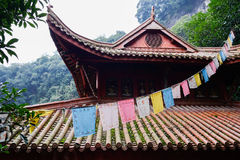 Colorful praying flags before ancient Chinese building in mounta Royalty Free Stock Photo