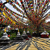 Colorful praying flags in Nepal over white stupas - buddhist religious buildings. Royalty Free Stock Photos
