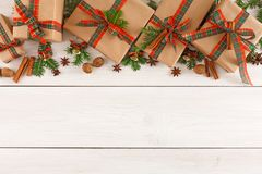Colorful present boxes for any holiday on wooden background. Gift boxes, nuts, small bells and fir tree twigs border, top view with copy space on wood table Royalty Free Stock Photo