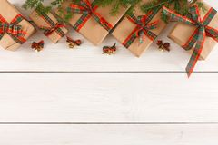 Colorful present boxes for any holiday on wooden background. Gift boxes, small bells and fir tree twigs border, top view with copy space on wood table background Royalty Free Stock Images