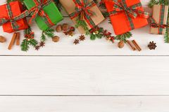 Colorful present boxes for any holiday on wooden background. Gift boxes, nuts, small bells and fir tree twigs border, top view with copy space on wood table Royalty Free Stock Images