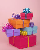 Colorful present boxes with ribbon stacked asymmetrically. And randomly on a textured pink background Royalty Free Stock Images