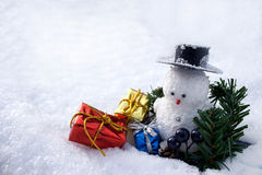 Colorful presents and a snowman. Presents around a snowman sitting on snow Royalty Free Stock Photography