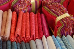 Colorful and printed textile fabrics in small bundles. Red and blue printed textile fabric sheets ordered by colors and in small bundles Royalty Free Stock Photos