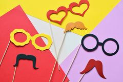 Colorful props for party. Carnival accessories set. Paper glasses, hat, lips, moustaches, tie on wooden sticks. Colorful props for party. Carnival accessories stock images