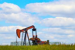 Colorful pump jack on oil well - low horizon on prairie with green grass and wild flowers - big blue cloudy sky - room for text Royalty Free Stock Photo
