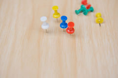 Colorful  push pin marking on wooden floor for background Stock Photos