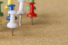 Colorful push pins on cork bulletin board. Royalty Free Stock Images