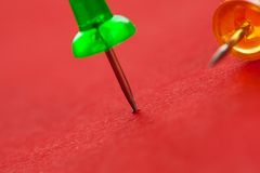 Colorful pushpins on a red surface Stock Photos