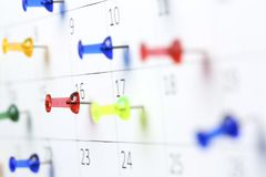 Pushpins on calendar. Colorful pushpins on white calendar clsoe up, shallow dof Royalty Free Stock Photo