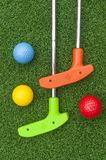 Colorful Putt Putt clubs and Balls. Two colorful putt putt clubs and balls outdoors on artificial grass Royalty Free Stock Photography