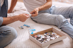 Colorful puzzle elements in hands of two male friends. Joyful game. Numerous colorful small puzzle pieces lying in the box and on the bed while being the part of Royalty Free Stock Photo