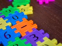 Colorful puzzle Jigsaw plastic number on the wooden table. Concept of education and math learning.  royalty free stock photo