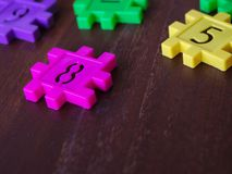 Colorful puzzle Jigsaw plastic number on the wooden table. Concept of education and math learning. Colorful puzzle Jigsaw plastic number on the wooden table royalty free stock photo