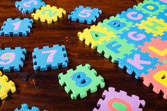 Colorful puzzle letters on wooden background Royalty Free Stock Photography