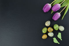 Colorful quail eggs and tulip flowers and green wooden birds on stone table. Top view with copy space stock photos