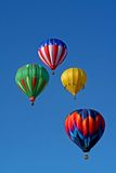 Colorful Quartet. A group of four colorful hot air balloons soar in a beautiful blue sky Royalty Free Stock Photo