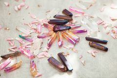 Colorful quartz crystals with pink rose leaves on wooden structure stock image