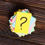 Colorful question marks written reminders tickets on wooden background.  Stock Photos