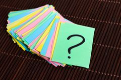 Colorful question marks written reminders tickets on wooden background.  Royalty Free Stock Image