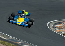 Colorful race car, Number 99. MW a blue and yellow formula 5000 race car going through the apex of a corner Royalty Free Stock Photo