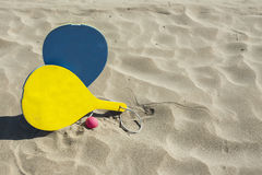 Colorful rackets and a ball in the sand of the beach in a sunny Stock Photo