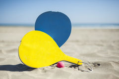 Colorful rackets and a ball in the sand of the beach in a sunny Royalty Free Stock Photo