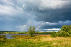 Colorful rainbow against the cloudy sky. Colorful rainbow in the background of a beautiful cloudy sky in summer windy day Royalty Free Stock Photo