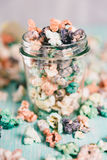Colorful rainbow candy popcorn. Fruit flavored popcorn in glass jar. Sugared popcorn texture Stock Image