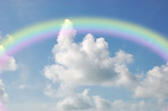 Rainbow in the Clouds. Colorful rainbow in cloudy blue sky Stock Photography