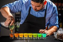 Colorful rainbow cocktails. Dozen of colorful rainbow cocktails being prepared on the counter by a bartender royalty free stock image
