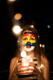 Colorful rainbow face art on a young girl at night with lights in a hands and bokeh. Girl with brown eyes, night city view royalty free stock photo