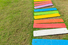 Colorful rainbow foot path garden decoration. Funny park background Royalty Free Stock Photos