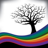 A colorful rainbow frames a bare tree Stock Images