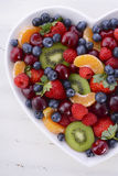 Colorful rainbow fruit in heart shape bowl. Stock Image