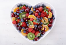 Colorful rainbow fruit in heart shape bowl. Colorful rainbow fruit including raspberries, strawberries, cherries, blueberries, mandarins and kiwi fruit  in Royalty Free Stock Photography