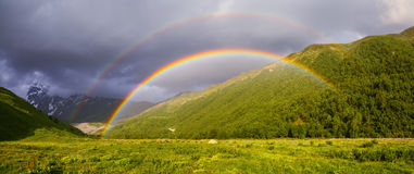 Colorful rainbow among high mountains. royalty free stock photography