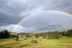 Colorful rainbow over alpine meadows with wooden huts Royalty Free Stock Photos