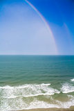 Colorful Rainbow over the Beach Shoreline. A colorful rainbow after a thunderstorm over crashing beach waves Stock Image
