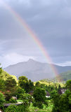 Colorful rainbow over the mountains Stock Image