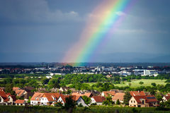 Colorful rainbow over the village Royalty Free Stock Photo