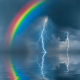 Colorful rainbow over wate. R, thunderstorm with rain and lightning on background Stock Photos