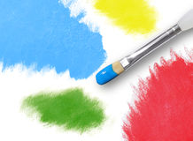 Colorful Rainbow Paint Splatters and Paintbrush. There are different splatters of paint in red, yellow, green and blue on an isolated background. A paint brush Stock Image