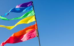 Colorful rainbow triangle flag shows up against the blue sky. stock image