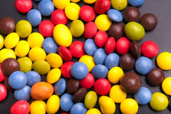 Colorful random chocolate sweets isolated on grey Royalty Free Stock Photos